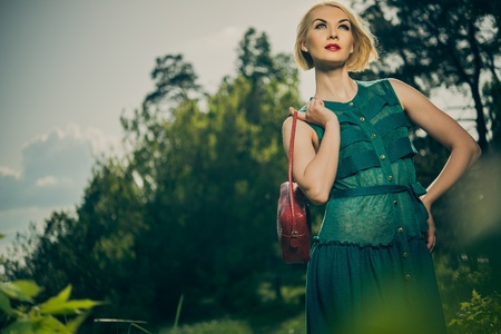 Beautiful blond woman with red bag in green dress outdoors  photo