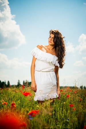 Beautiful young brunette girl wearing white summer dress in poppy filed photo