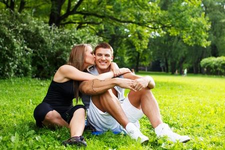 jovenes enamorados: Joven feliz pareja deportiva sonriente sentado en un prado en un parque