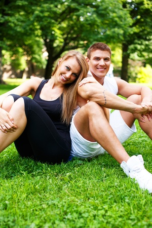 young girl smiling: Young happy smiling sporty couple sitting on a meadow in a park