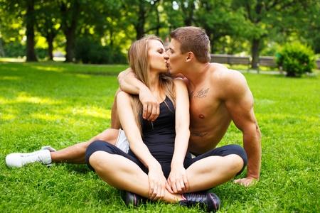 jovenes enamorados: Joven pareja feliz sonriendo deportivo besos en un prado en un parque Foto de archivo