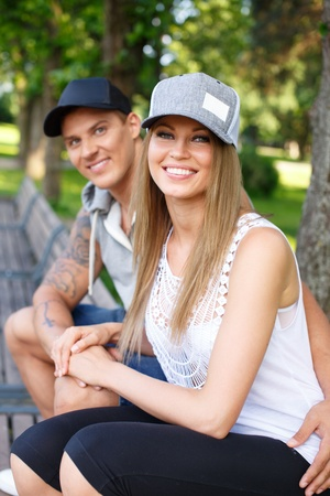 young lovers: Young happy smiling sporty couple sitting on bench in a park Stock Photo