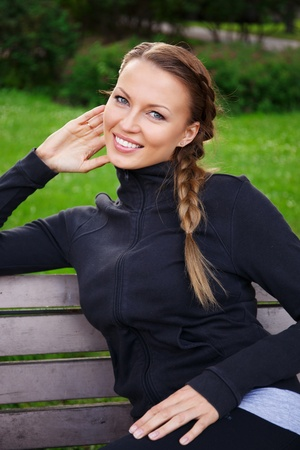 Young beautiful sporty brunette woman sitting on a bench in a park photo