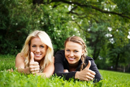 Two beautiful smiling girls lying on a grass in a park with thumbs up photo