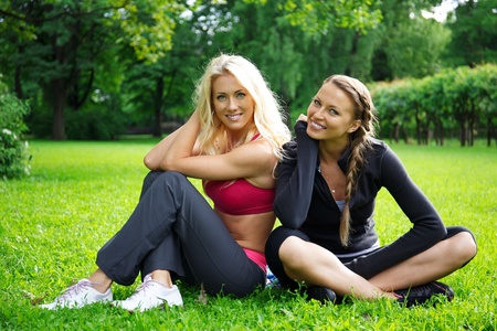 Two smiling athletic girls sitting on a grass in a park photo