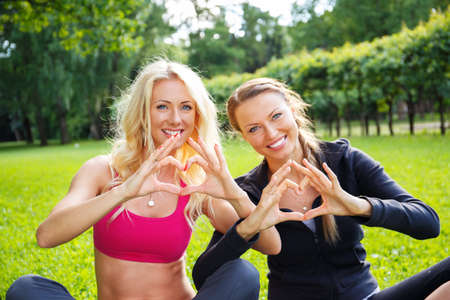 Young happy sporty girls showing heart sign with their hands on a meadow in a park photo