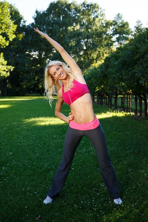 Young smiling blond athletic girl doing exercises on grass in a park and listens to music photo