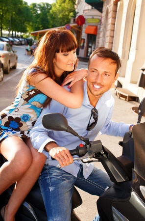 Happy middle-aged couple sitting on a scooter outdoors photo