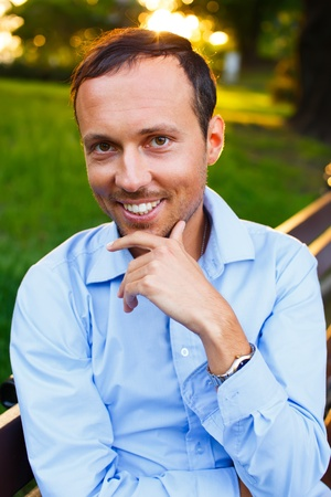 Happy handsome middle-aged man sitting on a bench outdoors  photo