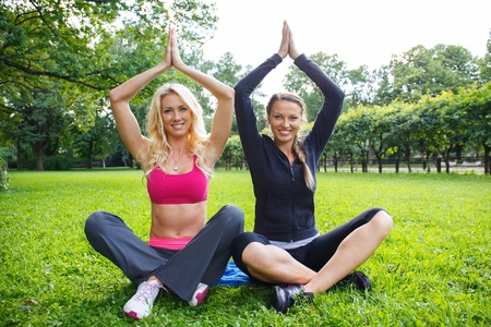 Two smiling athletic girls sitting in yoga pose on a grass in a park photo