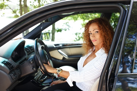 chauffeur: Beautiful middle-aged redhead woman behind steering wheel