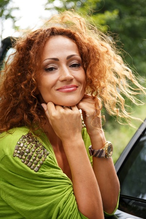 beautiful redhead: Beautiful middle-aged redhead smiling woman outdoors