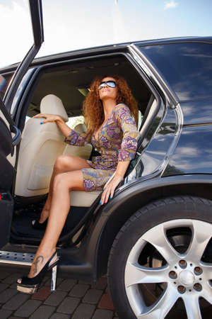 riches adult: Beautiful middle-aged redhead woman stepping out the car  Stock Photo
