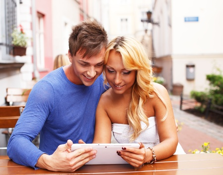 Stylish happy young couple with tablet pc behind table in a summer cafe photo