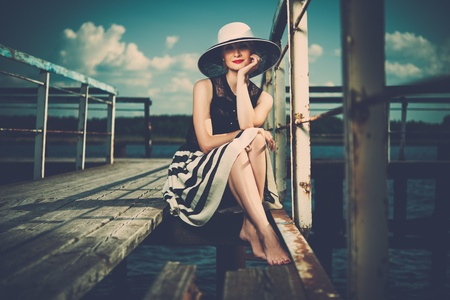 sepia toned: Beautiful woman wearing hat and white scarf sitting on old wooden pier  Stock Photo