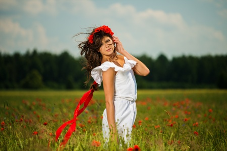 chaplet: Beautiful young brunette girl wearing white summer dress and flower chaplet in poppy filed