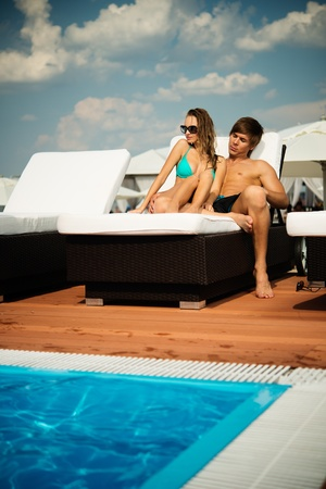 sea bed: Sexy young couple relaxing near pool on a beach bed