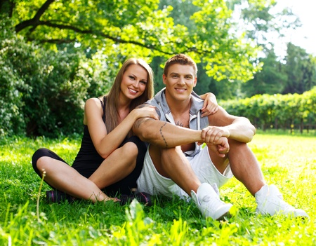 Young happy smiling sporty couple sitting on a meadow in a park photo
