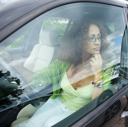 Beautiful middle-aged redhead woman behind steering wheel photo
