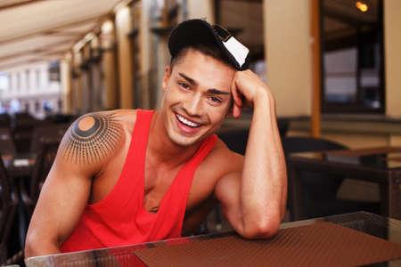 hombres gays: Hombre joven con estilo en el casquillo que se sienta detrás de la mesa en el café del verano