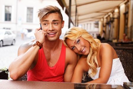 tatouage sexy: Élégant jeune couple avec un téléphone mobile derrière la table dans un café d'été