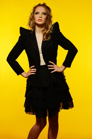 the girl in stockings: Beautiful young girl in black jacket and skirt isolated on yellow background  Stock Photo