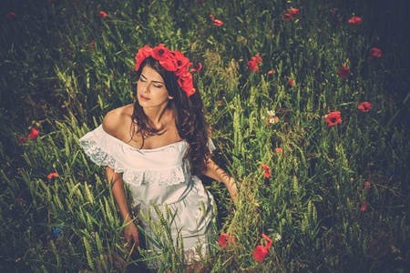 Beautiful young brunette girl wearing white summer dress and flower chaplet in poppy filed photo