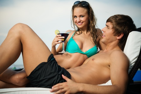 Sexy young couple relaxing with cocktail on a beach bed  photo