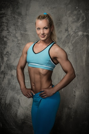 Beautiful bodybuilder woman on concrete background  photo