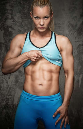 bicep: Attractive bodybuilder girl showing her abdominal muscles  Stock Photo