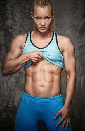 culturista: Chica fisicoculturista atractiva que muestra sus músculos abdominales