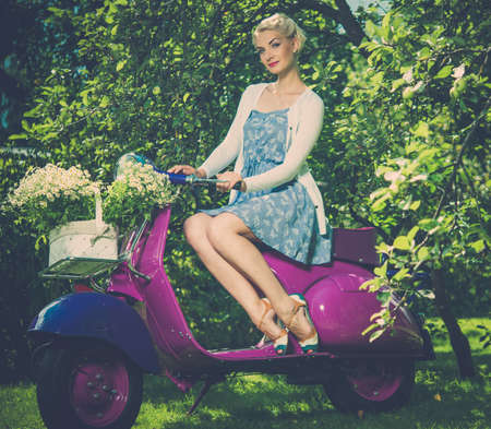 Beautiful blond woman sitting on a retro roller  photo