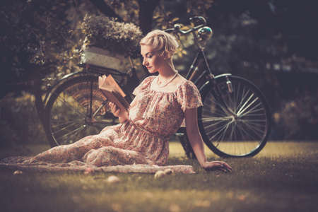 Blond beautiful retro woman reading book on a meadow Stock Photo - 21777537