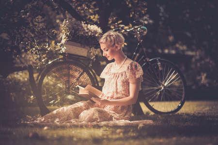 lezing: Blonde mooie retro vrouw lezen boek op een weide Stockfoto