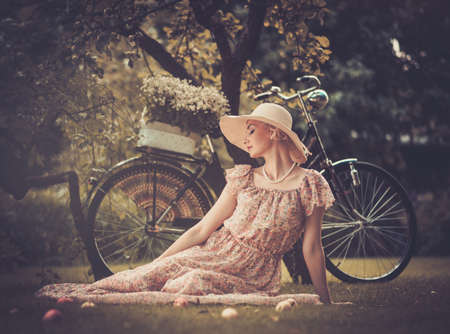 Beautiful dreaming blond retro woman with bicycle behind her photo