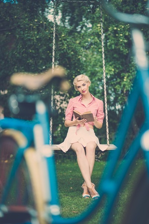 Beautiful blond retro woman sitting on a swings with a book Stock Photo - 21777576