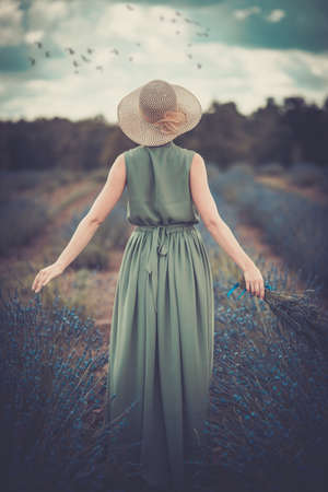 day dreaming: Woman in long green dress and hat in a lavender field