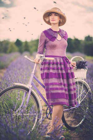 france perfume: Woman in purple dress and hat with retro bicycle in lavender field