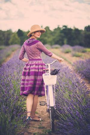 retro bicycle: Mujer en traje y sombrero p�rpura con la bicicleta retro en el campo de la lavanda Foto de archivo