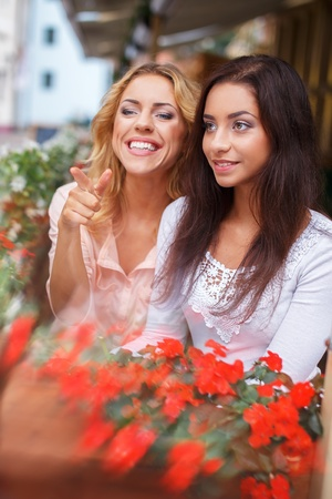 among: Two beautiful girls among flowers outdoors in a city