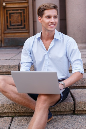 boy beautiful: Handsome young man with laptop sitting on a steps outdoors Stock Photo