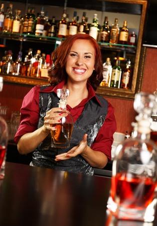 beautiful redhead: Beautiful redhead barmaid with bottle behind bar counter