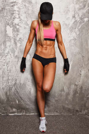 fitness trainer: Sporty woman in pink top with beautiful beautiful body against concrete wall