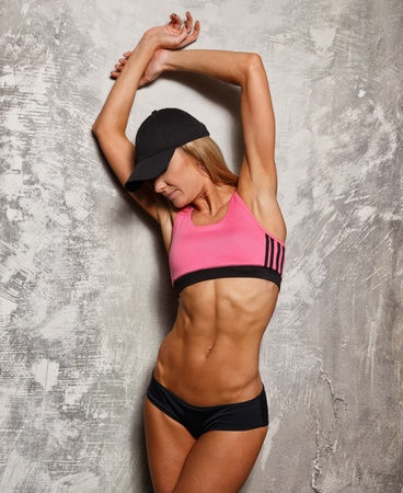 beautiful body: Sporty woman in pink top with beautiful beautiful body against concrete wall
