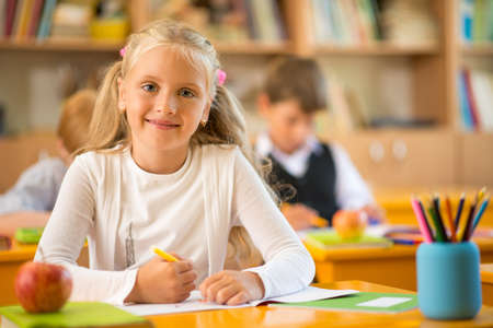 grade: Little schoolgirl sitting behind school desk during lesson in school Stock Photo