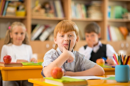 elementary: Little redhead schoolboy behind school desk during lesson Stock Photo