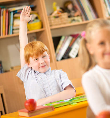 classmates: Little redhead schoolboy behind school desk during lesson with his hand up