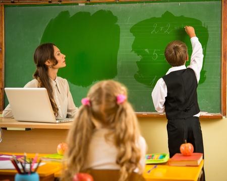 answering: Little schoolboy answering near blackboard in school
