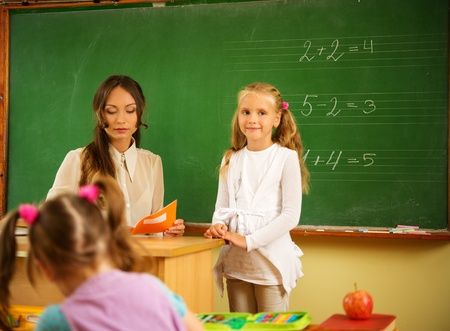 answering: Little schoolgirl answering near blackboard in school Stock Photo