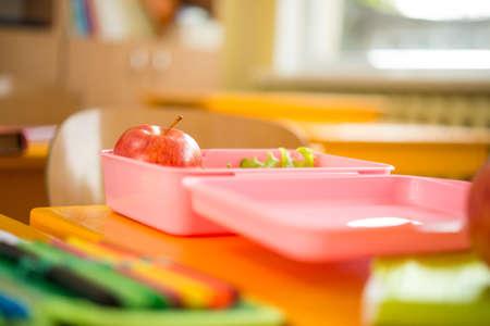 niños desayunando: Envase de alimento con manzana y ensalada en el aula